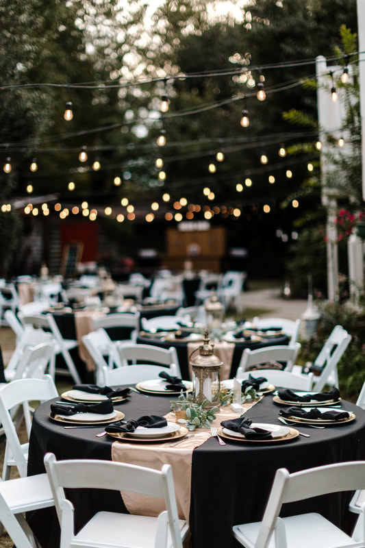 wedding reception tables under bistro lights with black linens and champagne decorations