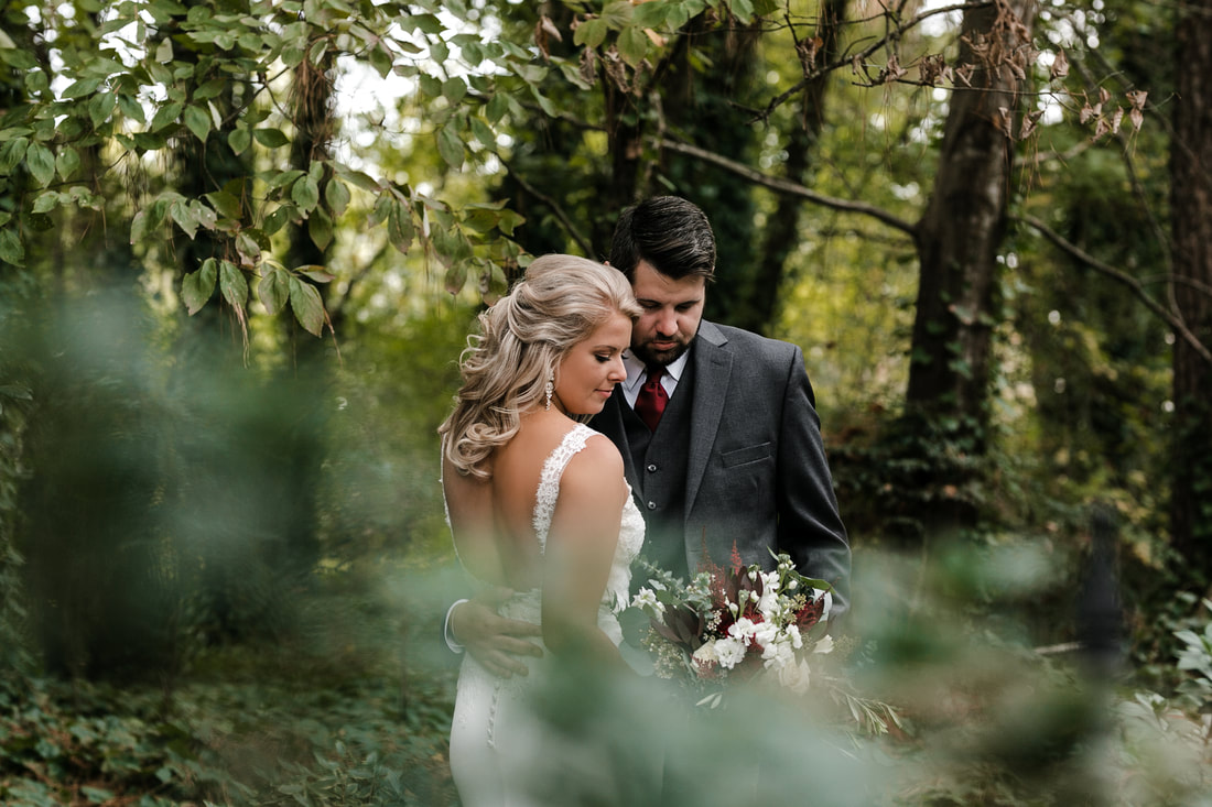 Bride and groom surrounded by trees and vibrant greenery at outdoor venue. Photographer created blur effect with leaves by focusing the lens on the couple.