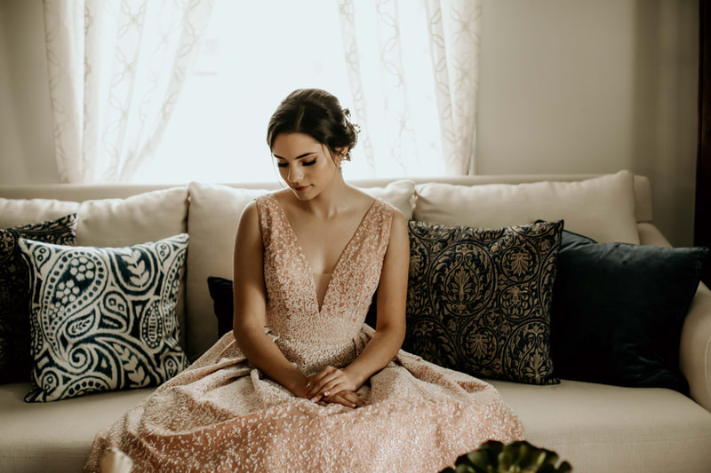 birthday girl in sparkly dress sitting on cream couch with blue pillows