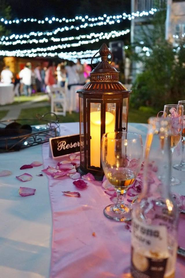 reserved table with bronze lantern and pink flower petals