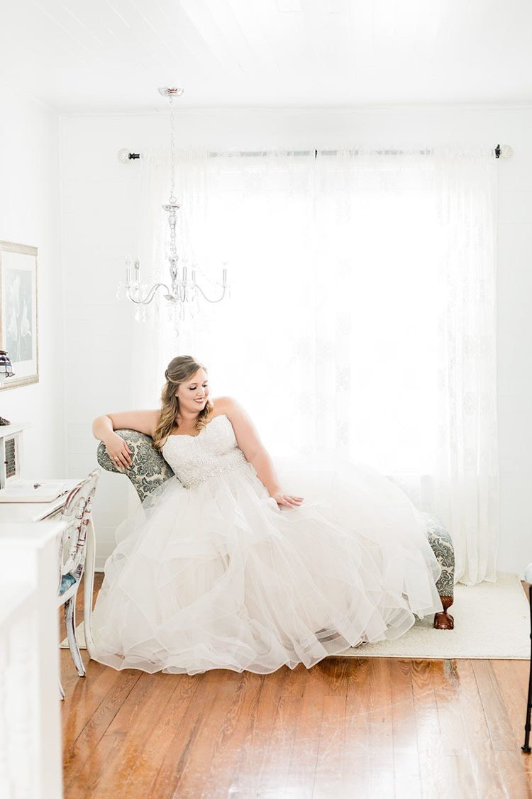 bride in ball gown wedding dress posing on farmhouse's chaise longue