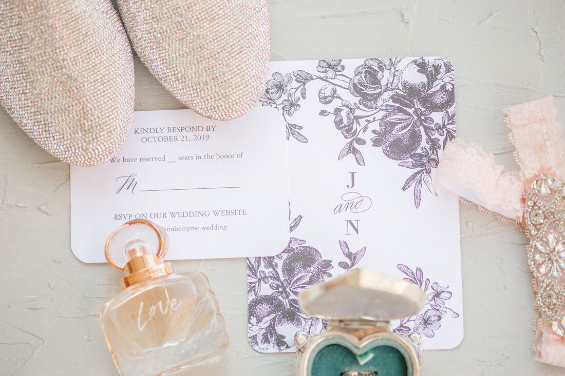 Flat lay with bride's shoes, perfume, garter, rings, and muted floral invites