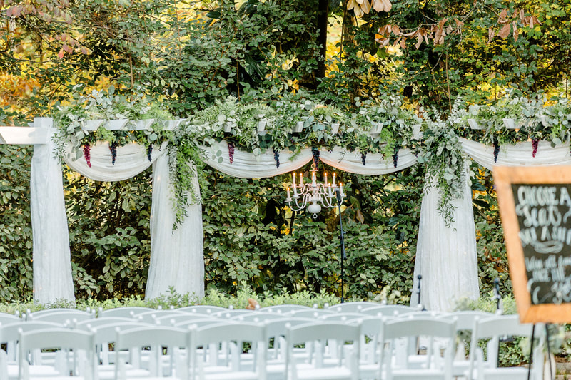 arbor decorated with white chiffon, full draping greenery, a chandelier, and grapes lining the top
