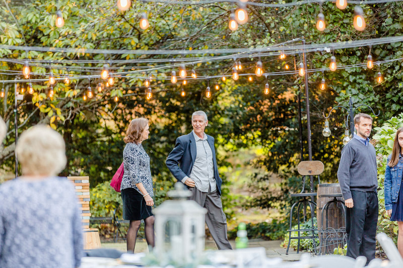 guests chatting during outdoor reception under string light bulbs