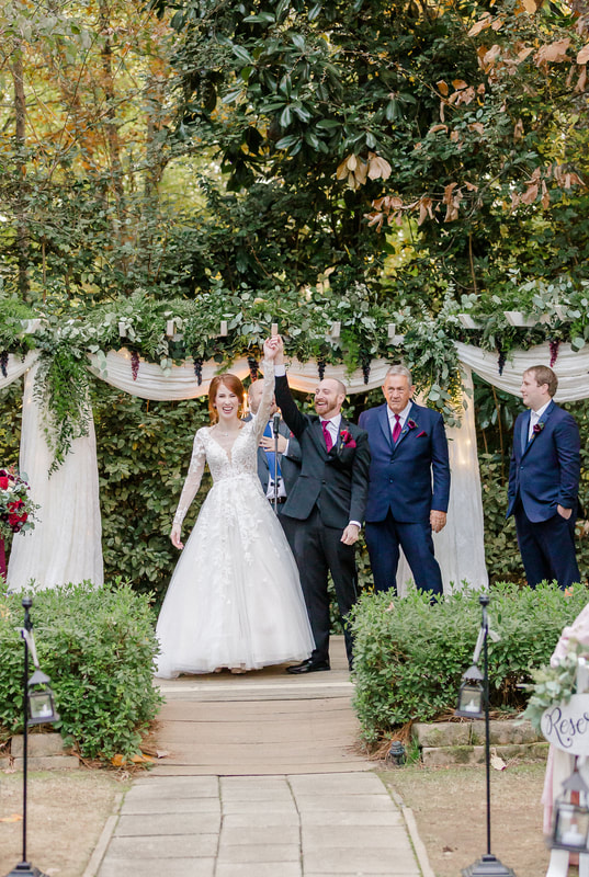 newly married couple holds hands up in celebration after vows