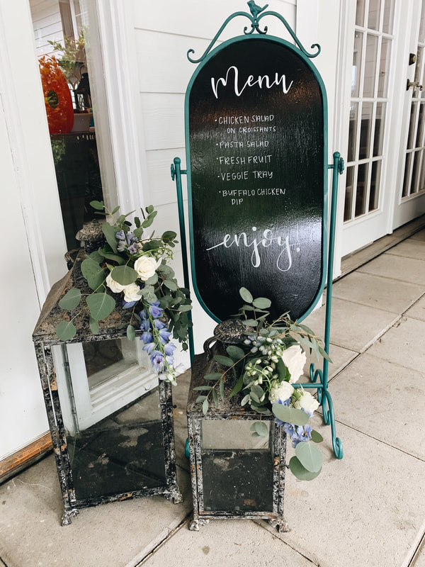 menu chalkboard sign by antique lanterns decorated with florals and greenery