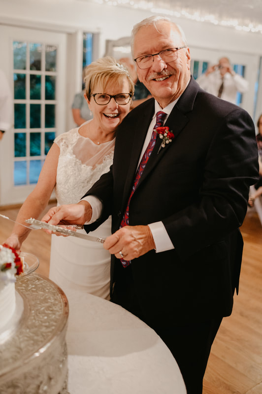 older couple cutting wedding cake