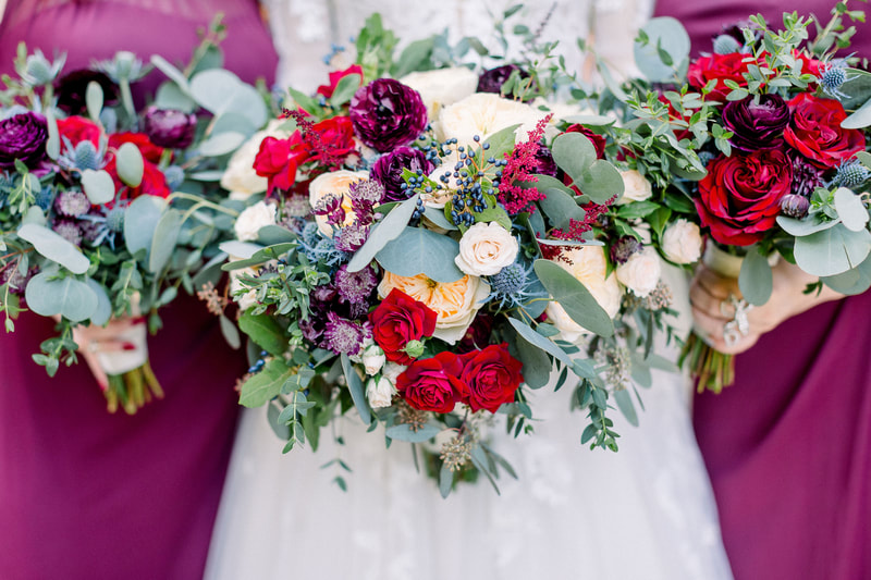 brides and bridesmaids' bouquets with ecclectic mix of red and white roses with purple, blue and white flowers, berries, and eucalyptus leaves