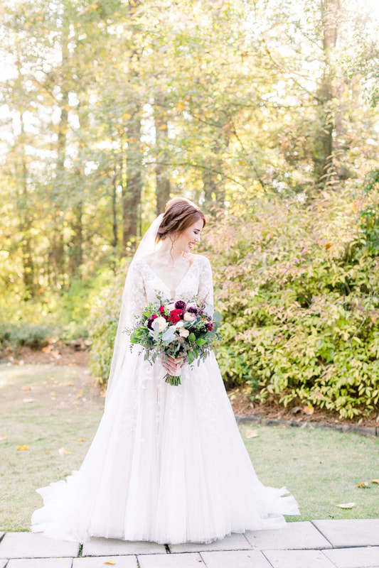 redhead bride in Four Oaks' gardens and outdoor venue holding larger, romantic bouquet with berries, leaves and flowers