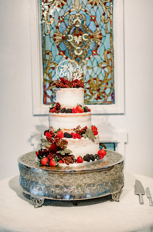 naked wedding cake with mixed berries and cake topper