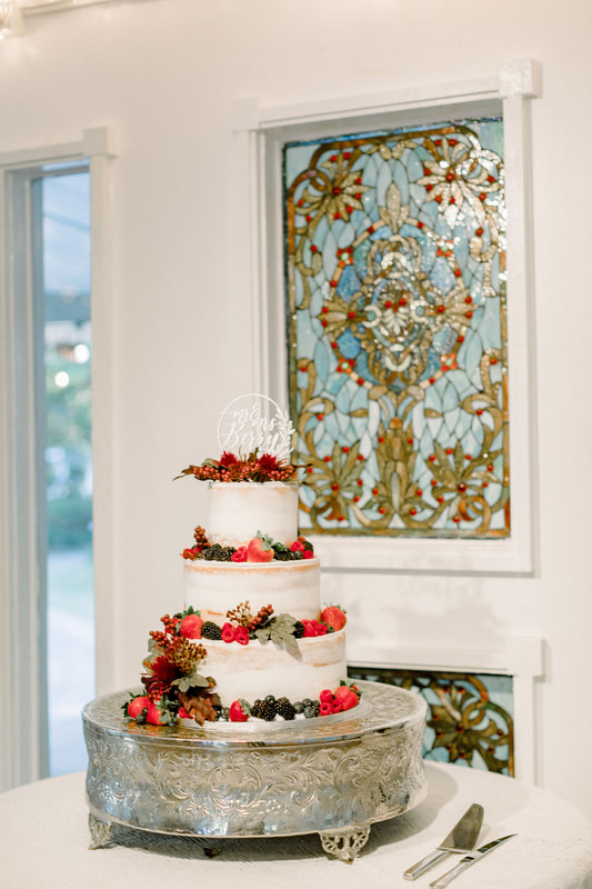 naked wedding cake decorated with strawberries, raspberries, and blackberries