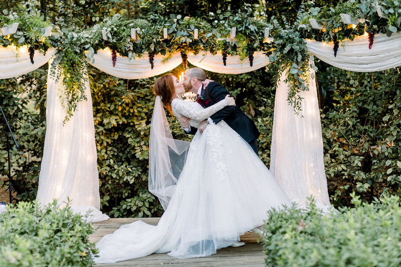groom dips bride at altar for a kiss with chandelier lit and grapes and greenery on arbor