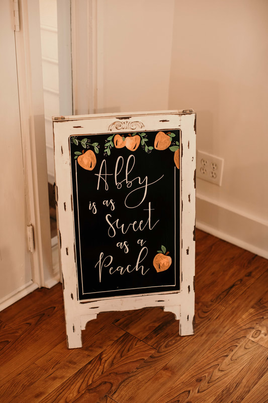 white chalkboard sign says 'abby is as sweet as a peach' with hand drawn peaches