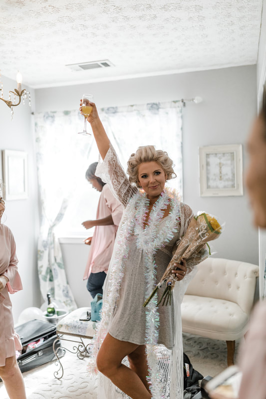 bride with flowers and mimosa with hair in rolls in bridal suite