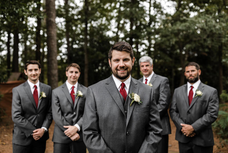groom with groomsmen in matching grey suits and red ties