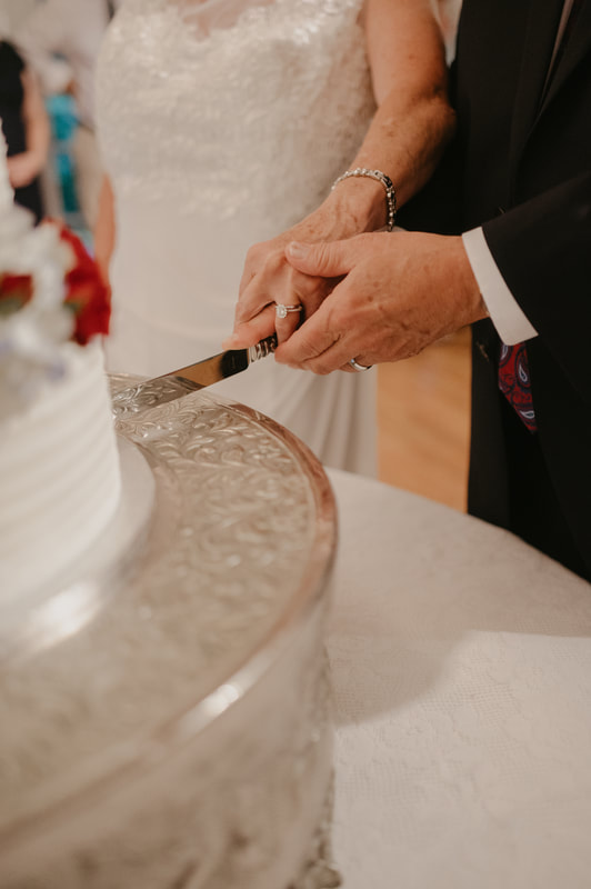 Couple cutting wedding cake together.