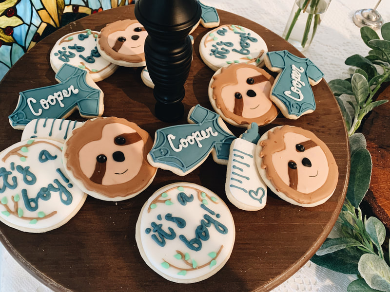 custom cookies with sloth faces, baby bottle, it's a boy!, and onsies