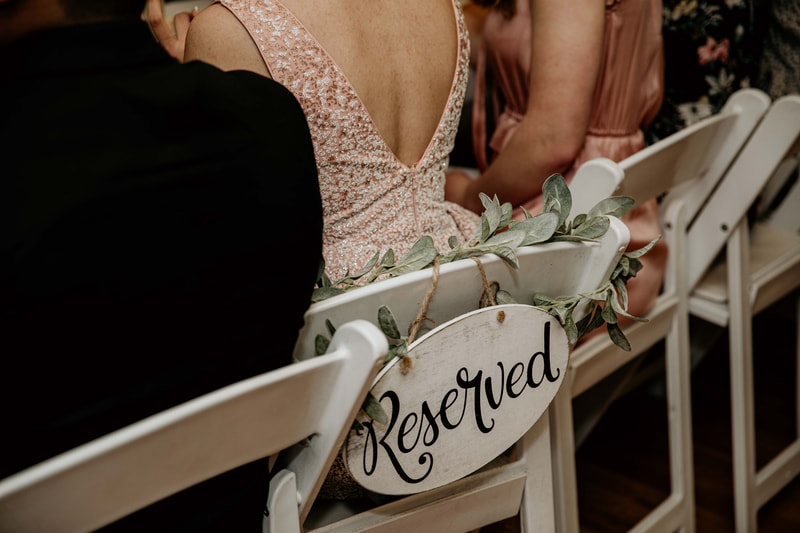 reserved sign on back on white chair with lambs ear greenery