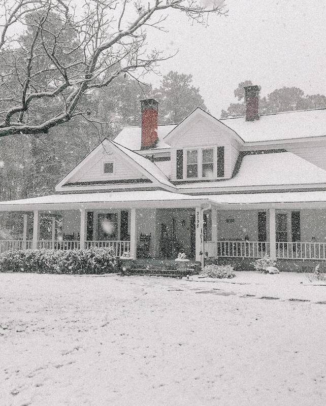 Four Oaks Manor farmhouse covered in snow
