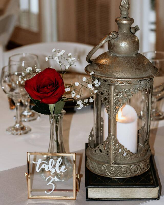 beauty and the beast themed tasting with antique lantern and a rose in a vase with baby's breath