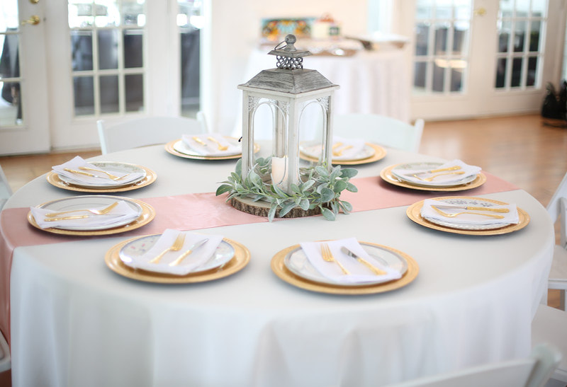 table setup for girl baby shower with pink runner, gold place settings, and ash grey lantern