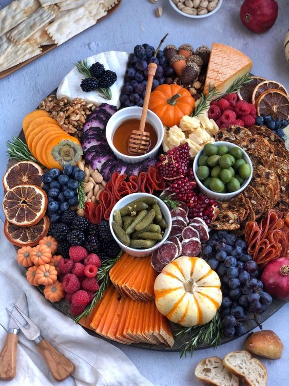 round charcuterie board with fall foods and colors and mini pumpkins