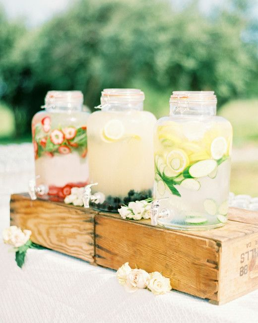 large mason jars on wood crate filled with water flavored with berries, lemon slices, and mint