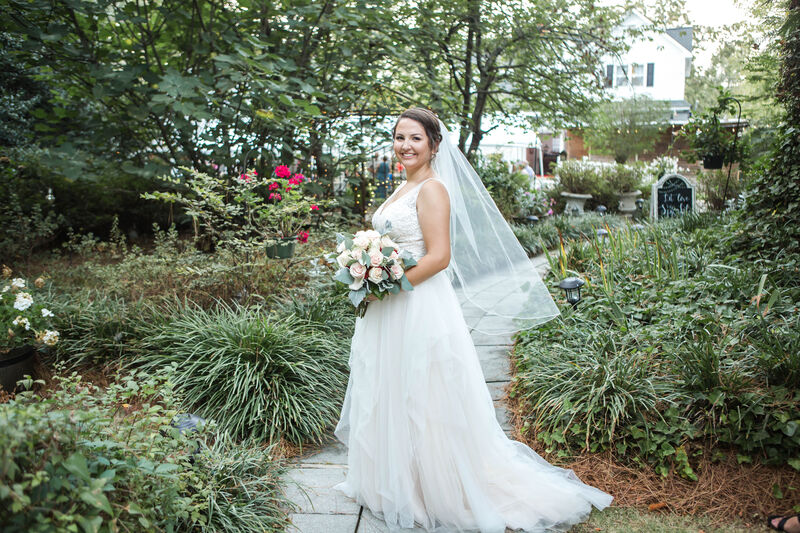 bride posing along pathway surrounded by green bushes and plants