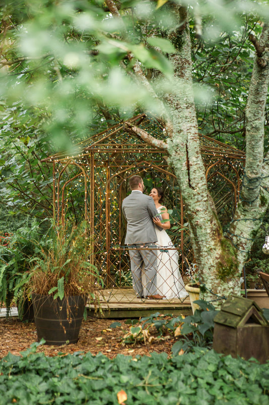 newlywed sharing first dance in gazebo wrapped in string lights surrounded by woods