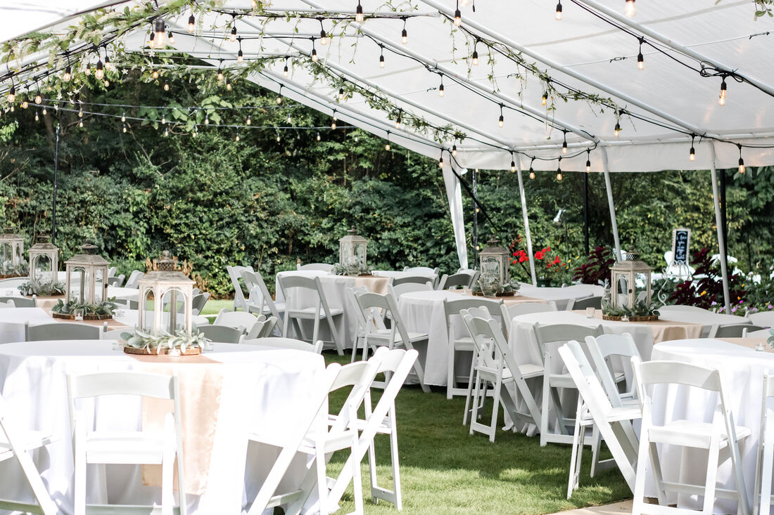 outdoor wedding reception under white tent with string lights and hanging greenery