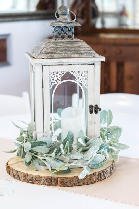 ash grey wooden lantern with LED candle and lambs ear greenery