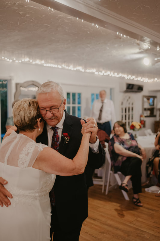Married couple sharing first dance in carriage house