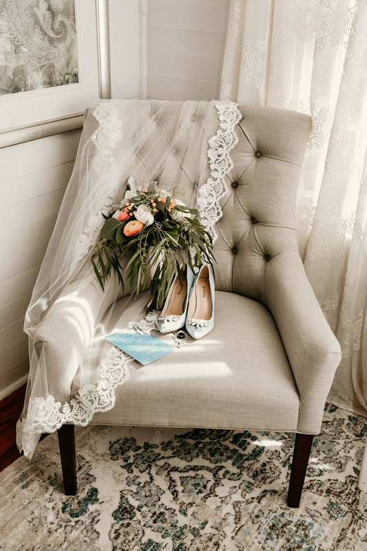 bride's vintage-inspired veil, bouquet, and wedding shoes on gray chair