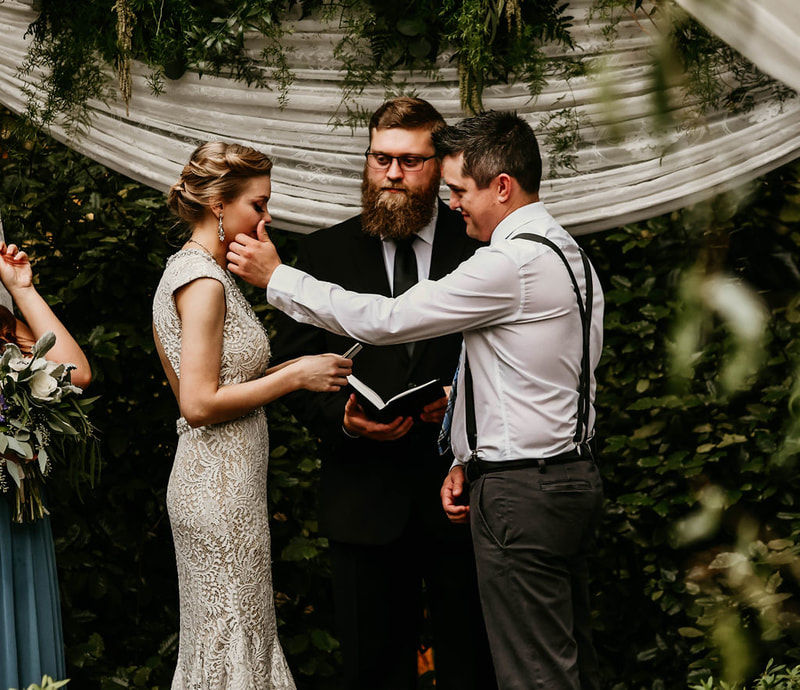 groom wiping tear from bride's face as she reads wedding vows