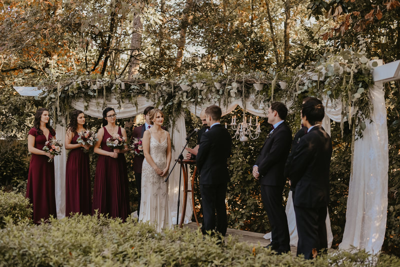 groom giving vows during November wedding with extravagantly decorated arbor with greenery and flowers
