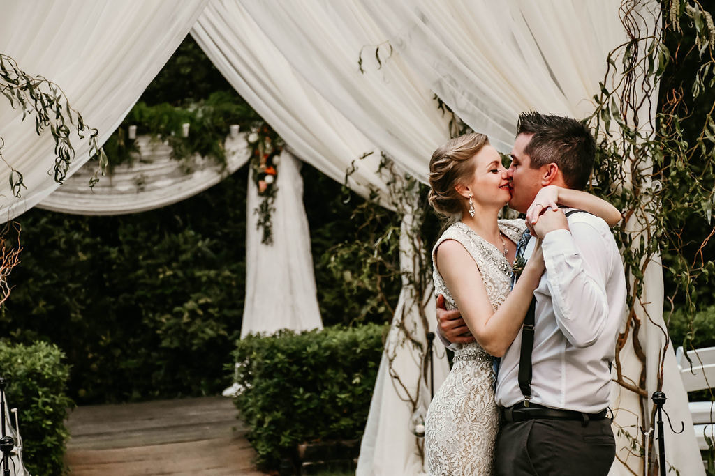 couple kissing in ceremony aisle surrounded by white drapes and hanging willow branches