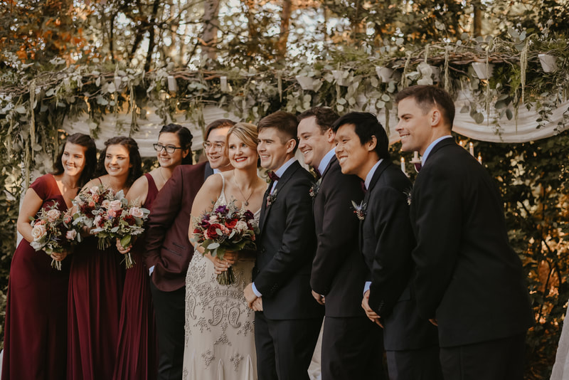 couple plus bridal party smile at altar for photos