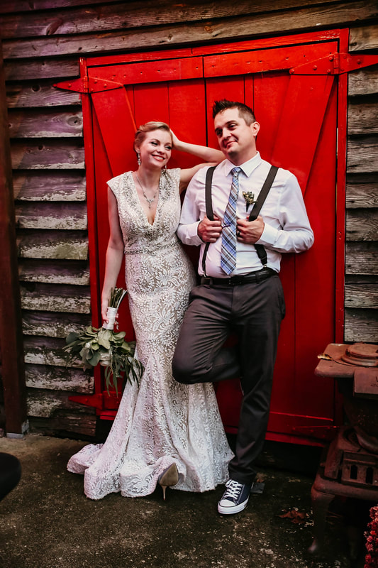 newlyweds posing by red door of smokehouse