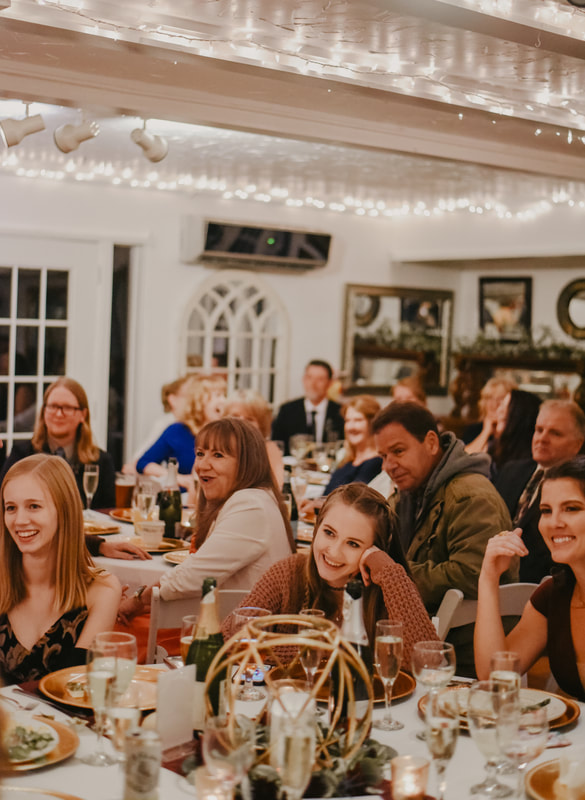 guests sitting inside the carriage house during indoor fall reception listening to toasts