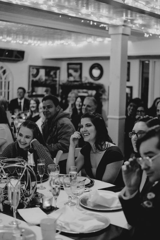 black and white photo of guests laughing to toasts inside Four Oaks Manor's carriage house
