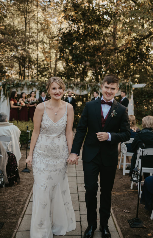 bride and groom walk down aisle together post-ceremony smiling and holding hands