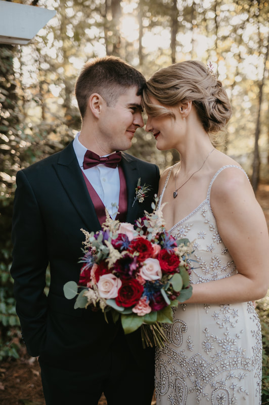married couple touch foreheads and smile while bride holding non-traditional bouquet