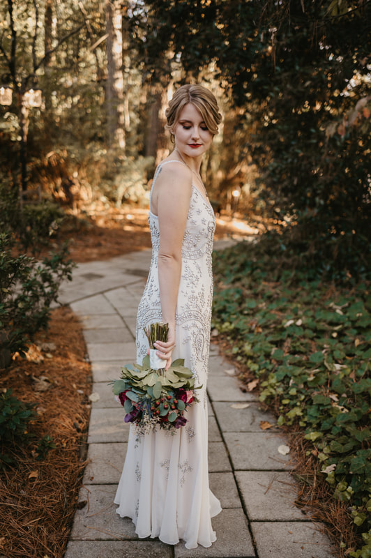 bride in simple, vintage dress holding bouquet while looking down