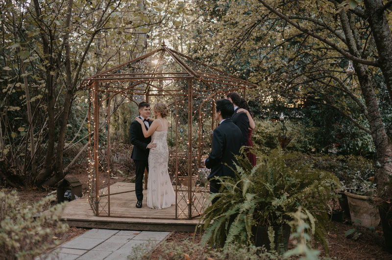 couple have first dance inside gazebo while guests watch outside
