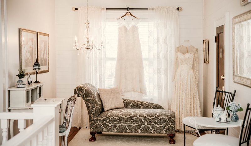 lace gown hangs against bright farmhouse windows