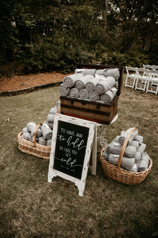 'to have and to hold in case you get cold' chalkboard sign with gray blankets for favors
