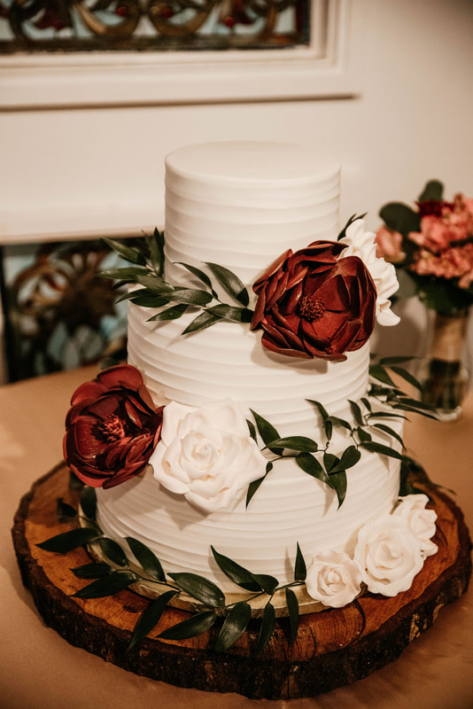 white wedding cake with leaves and white and burgundy flowers