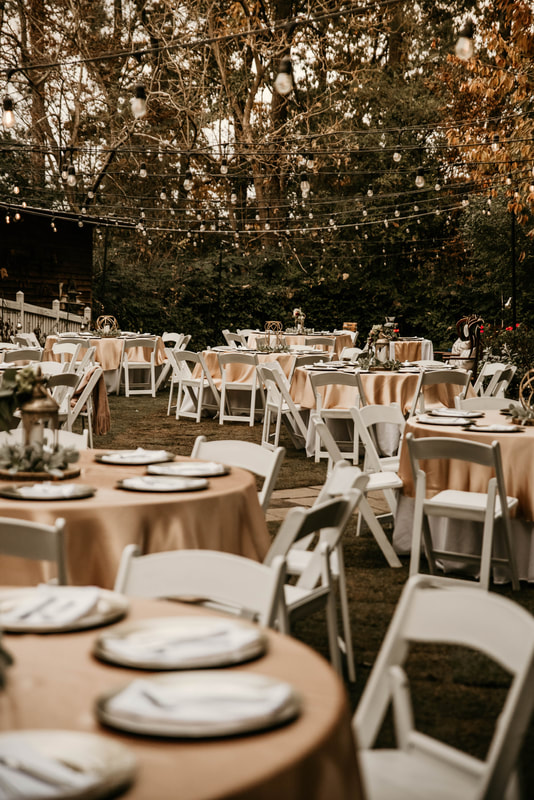 wedding reception area with gold table overlays and white chairs