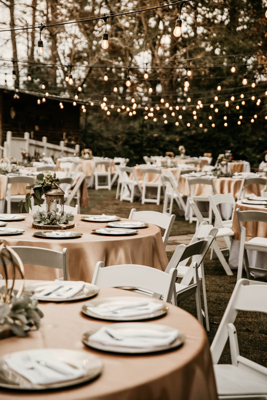wedding reception tables decorated with champagne overlays with gold centerpieces with greenery