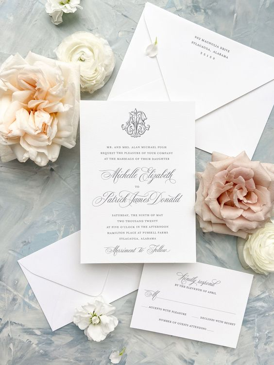 formal wedding invitations with blush and white flowers on flat lay display